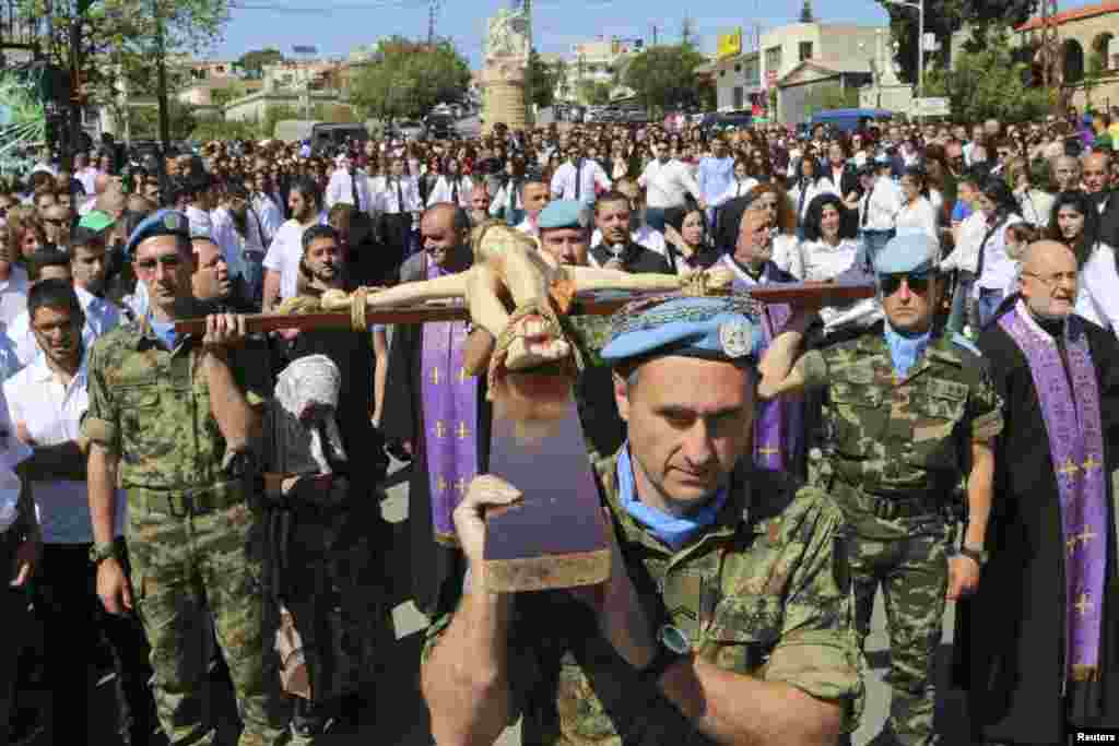 Serbian and Spanish U.N. peacekeepers carry a cross with a statue of Jesus Christ during a Good Friday ceremony in Kalayaa, Marjayoun countryside in south Lebanon, April 18, 2014.