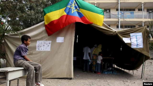 A boy sits outside a polling station, as Ethiopia's national election kicks off in capital Addis Ababa, May 24, 2015.