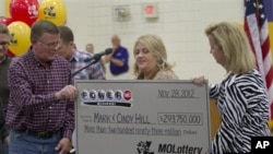 Mark (L) and Cindy (C) Hill are presented a check by a Missouri Lottery official during the announcement of Powerball winners in Dearborn, Missouri, November 30, 2012.