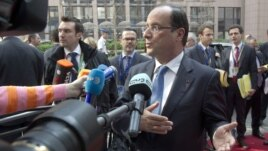 French President Francois Hollande gestures as he speaks to reporters upon his arrival for an EU summit, at the European Council building in Brussels, May 23, 2012.