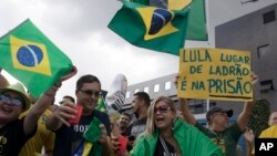 "A demonstrator holds up a sign that reads in Portuguese ""Lula, a thief's place is in prison"" as people shout slogans against Brazil's former President Luiz Inacio Lula da Silva in front of the Federal Police Department in Curitiba, Brazil, April 6, 2018."