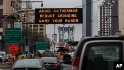 In this March 19, 2020, file photo, the Manhattan bridge is seen in the background of a flashing sign urging commuters to avoid gatherings, reduce crowding and to wash hands in the Brooklyn borough of New York. The coronavirus pandemic is leading to infor