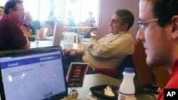 Seorang pengguna facebook tengah mengamati layar monitor laptopnya di sebuah universitas di Wisconsin-Madison (Foto: dok). Facebook menjadi perusahaan pertama yang merilis angka agregat permintaan pengintaian dari pemerintah AS.