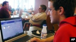 In this April 18, 2013, photo sophomore Mike Ziehr looks at his computer in the student union at the University of Wisconsin at Madison.