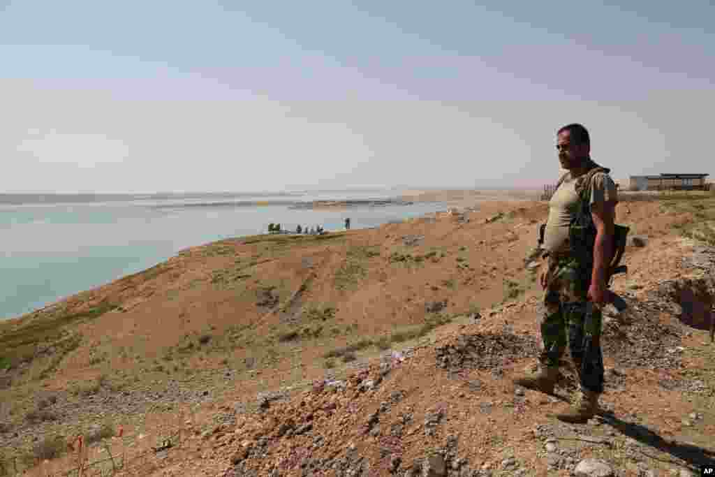 A Kurdish peshmerga fighter stands guard at the Mosul Dam, near the town of Chamibarakat, outside Mosul, Iraq, Aug. 17, 2014.