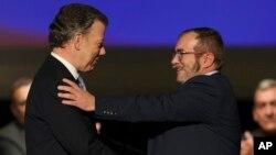 En esta foto de archivo se ve al presidente de Colombia Juan Manuel Santos, (izquierda) saludando a Rodrigo Londoño, alias Timochenko, máximo líder de las FARC, tras firmar el acuerdo de paz en Bogotá, Colombia.