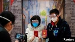 Cặp vợ chồng mới cưới vừa nhận giấy đăng ký kết hôn mang khẩu trang chụp hình lưu niệm tại Thượng Hải, Trung Quốc.