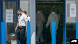"""Forensic police officers work at the supermarket where two people were injured when a woman shouting """"Allah akbar"""" (God is greatest) attacked two people with a boxcutter on June 17, 2018 in La Seyne-sur-Mer, southern France."""