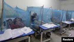 Một người phụ nữ giữ con trai, mắc bệnh sốt xuất huyết, khi ngồi dưới màn chống muỗi trong một bệnh viện địa phương ở Rawalpindi, Pakistan.