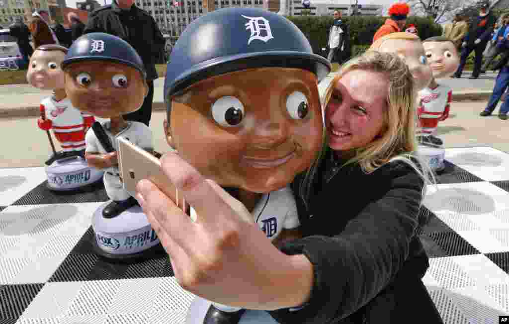 Katie Lanivich takes a photograph with a Detroit Tigers bobble head before a baseball game against the New York Yankees in Detroit, Michigan.