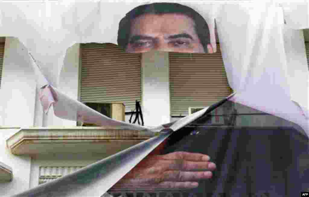 16 Ocak: Tunus'ta devrik Devlet Başkanı Zine el Abidin bin Ali'nin yırtılmış posteri. (AP/Christophe Ena)