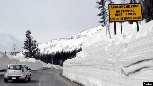 FILE - A car travels the newly plowed east entrance road over Sylvan Pass in Yellowstone National Park shortly after the park opened in this photo taken in May 2011.