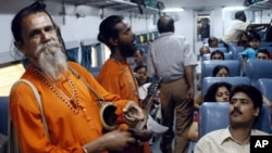 Indian 'Baul' singers perform the traditional Bengali songs of Rabindranath Tagore as they entertain passengers on board a train at Bolpur some 200 kms north of Calcutta, 11 June, 2004.