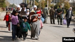 FILE - Syrian families leave the besieged town of al-Mouadamiya in Damascus countryside, Oct. 29, 2013.