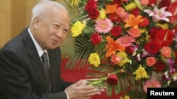 Cambodian King Norodom Sihanouk stands beside flowers given by the Chinese government during a meeting with Chinese State Councilor Dai Bingguo (not seen) in Beijing, October 30, 2006.