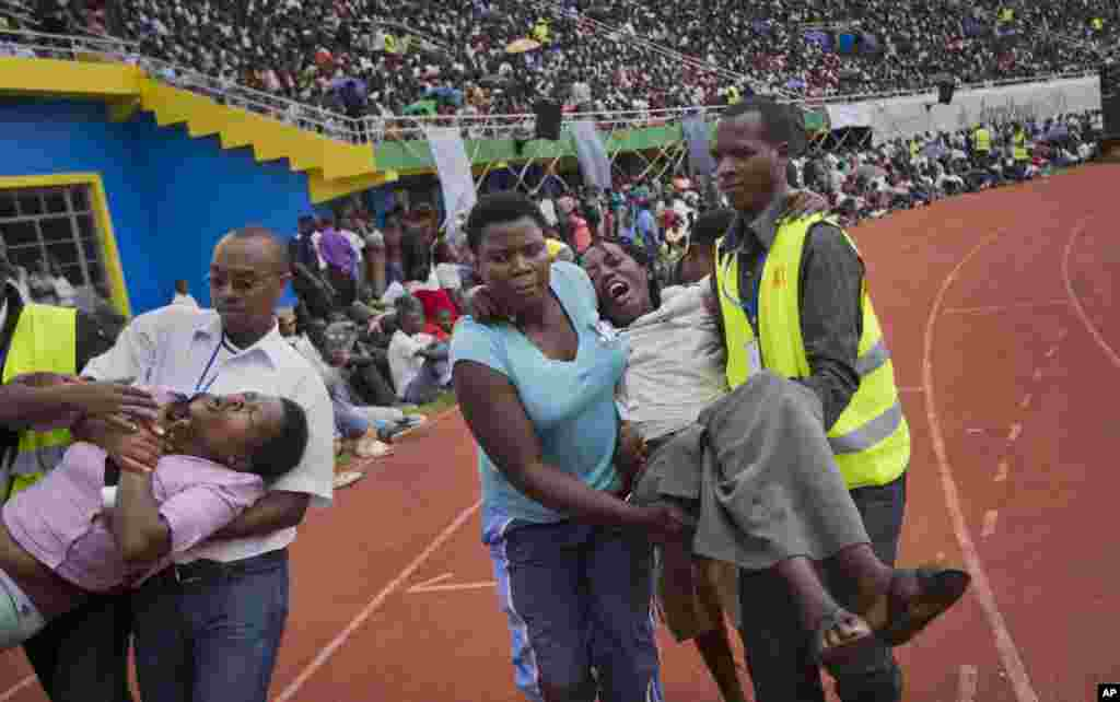 Two wailing women, some of dozens overcome by grief at recalling the horror of the genocide, are carried away to receive help during a ceremony to mark the 20th anniversary of the Rwandan genocide, at Amahoro stadium in Kigali, April 7, 2014.
