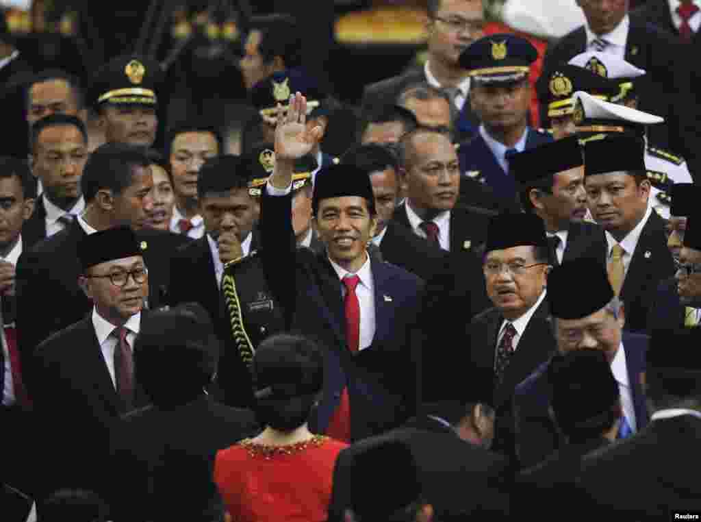 Presiden baru Joko Widodo meambaikan tangannya usai diambil sumpahnya di Gedung DPR di Jakarta (20/10), didampingi Wakil Presiden Jusuf Kalla.(Reuters/Darren Whiteside)