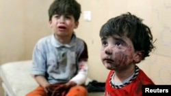 FILE - Injured children cry after, according to activists, two barrel bombs were thrown by forces loyal to Syria's president Bashar Al-Assad in Hullok neighbourhood of Aleppo.
