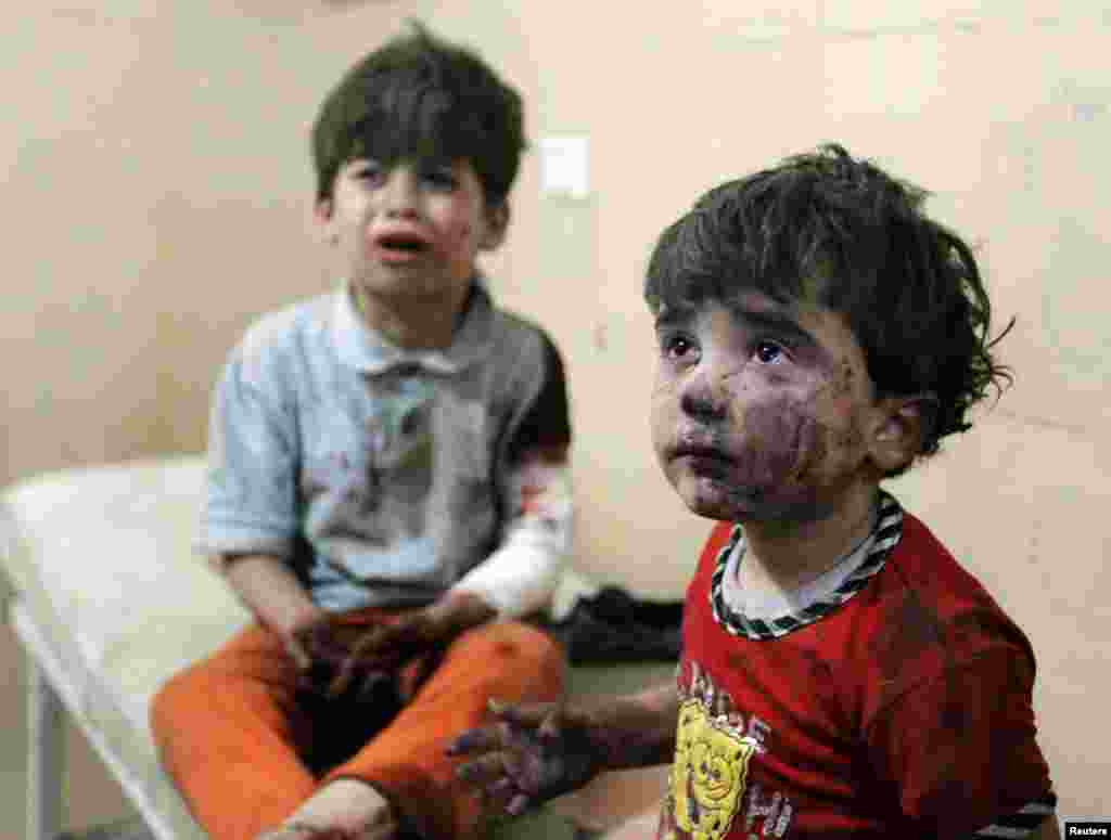 Injured children cry after, according to activists, two barrel bombs were thrown by forces loyal to Syria's president Bashar Al-Assad in Aleppo.