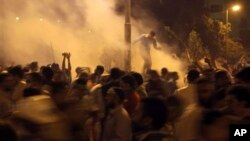 Supporters of Egypt's ousted President Mohammed Morsi run for cover from tear gas fired by riot police during clashes at Nasr City, where protesters have installed their camp and hold their daily rally, in Cairo, Egypt, July 26, 2013.