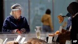 Seorang warga London dengan mengenakan pelindung wajah berbelanja di sebuah toko roti (foto: dok).