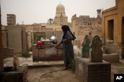 A woman who lives in the Cairo Necropolis cleans a tomb, outside her home in Cairo, Egypt, October 23, 2015. In the sprawling Cairo Necropolis, known as the City of the Dead, life and death are side by side.