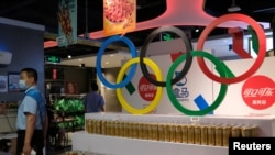 FILE - Olympic rings are seen above products of The Coca-Cola Company, a corporate sponsor of the Beijing 2022 Olympic Games, at a supermarket in Beijing, China, July 30, 2021.