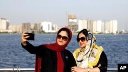 İran'ın başkenti Tahran'ın batısındaki Şehitler Gölü'nde iki İranlı kadın fotoğraf çekiliyor.
