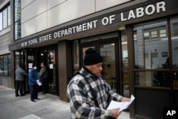 FILE - Visitors to the Department of Labor are turned away at the door by personnel due to closures over coronavirus concerns in New York, March 18, 2020.