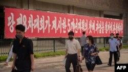 19일 북한 평양에 당 제8차대회가 제시한 과업을 관철하자는 내용의 구호가 걸려있다.