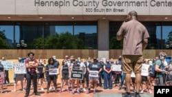 Para pengunjuk rasa berdemo di luar gedung Hennepin county Government Center, sebelum persidangan Derek Chauvin, mantan polisi yang terkait kasus kematian pria kulit hitam, George Floyd, 8 Juni 2020 di Minneapolis, Minnesota.