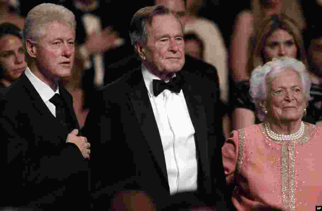 FILE- In this March 21, 2011, file photo, from left, former President Bill Clinton, former President George H.W. Bush and his wife Barbara Bush stand for the National Anthem at the Kennedy Center.