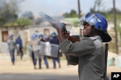 FILE: Armed Zimbabwean police battle rioters in Harare, Monday, July, 4, 2016