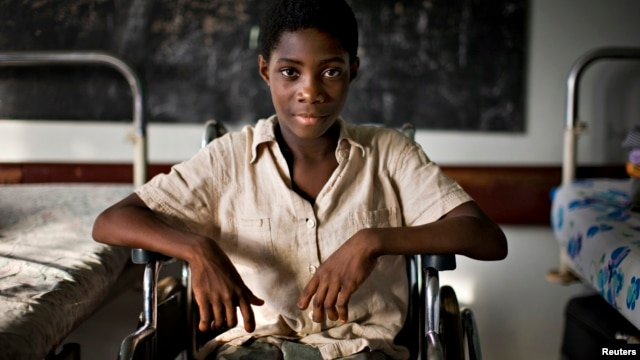 FILE - Marie-Madelaine Avouzoa, whose legs were amputated at the knees and lost her fingertips after a blood transfusion for malaria infected her limbs, sits in a wheelchair at the Center for the Rehabilitation of the Handicapped in Cameroon's capital, Yaounde on March 16, 2009.