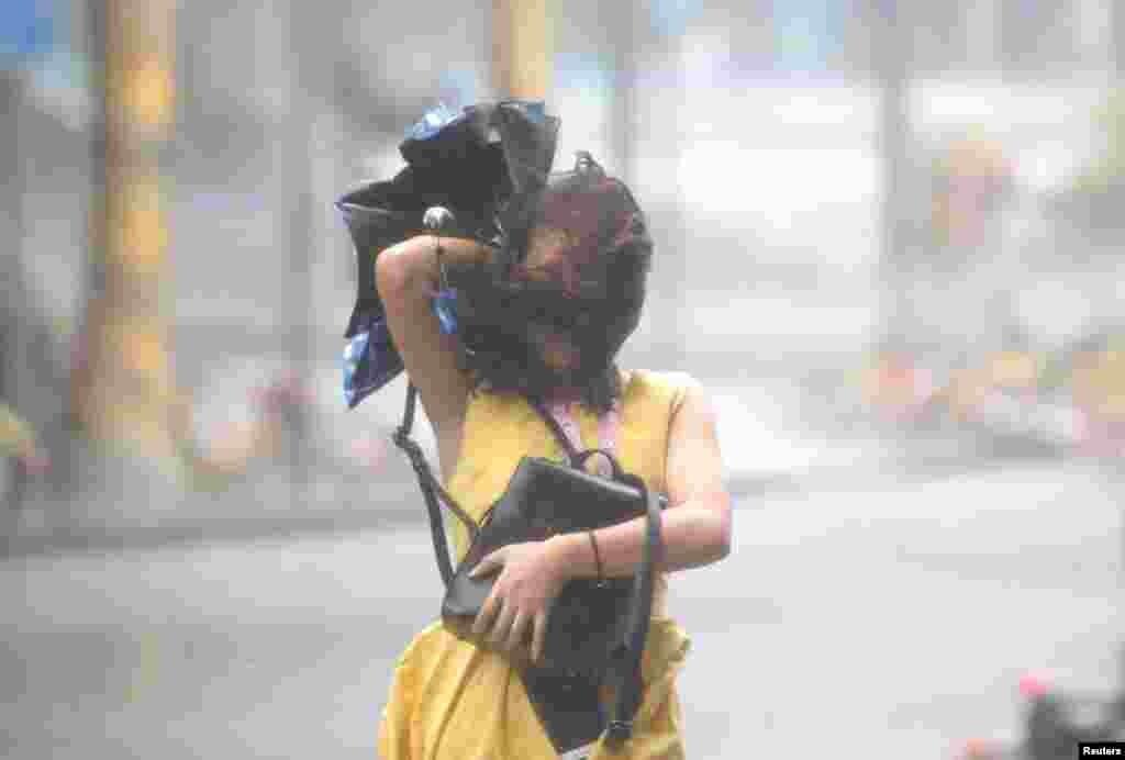 در فلیپین نیز یک ابرتوفان روی داد که دست کم بیست کشته برجای گذاشت. اکنون این توفان با شدت کمتر به سمت چین می رود و این زن جوان سعی دارد خود را به سرپناهی برساند.