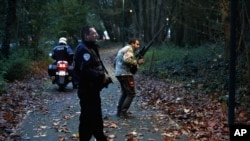 Members of the police animal brigade walk through a wood in Montevrain, east of Paris, Thursday Nov. 13, 2014.