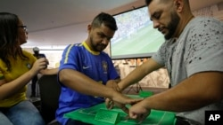 Brazil soccer fan Carlos Junior, who is both deaf and blind, experiences the World Cup match between Brazil and Mexico with the help of an interpreter who uses tactile signing and a model soccer field in Sao Paulo, Brazil, July 2, 2018. Brazil won the match 2-0.