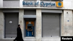 A Greek Orthodox priest walks a branch of Bank of Cyprus in Athens, March 19, 2013.