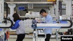 工人们在东莞一家工厂测试工业机器人。(2019年3月1日)