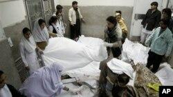 Nhân viên y tế và tình nguyện viên che phủ thi thể các nạn nhân vụ nổ bom, tại một bệnh viện ở Quetta, Pakistan, 16/2/2013