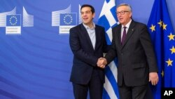 FILE - European Commission President Jean-Claude Juncker, right, welcomes Greece's Prime Minister Alexis Tsipras upon his arrival at the European Commission headquarters, Brussels, Feb. 4, 2015.