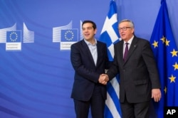 FILE - European Commission President Jean-Claude Juncker, right, welcomes Greece's PM Alexis Tsipras upon his arrival at the European Commission headquarters in Brussels, Feb. 4, 2015.