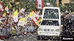Warga Katolik Lebanon melambaikan bendera Lebanon dan Vatikan saat mobil Paus Benediktus melewati jalan di Beirut (15/9).
