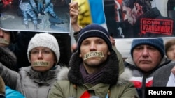 Pro-European integration supporters with taped mouths attend a rally against newly approved anti-protest laws in Kyiv, Jan. 17, 2014.