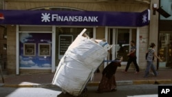 A scrap collector pulls her trolley in front of a Turkish bank in Istanbul, Tuesday, June 4, 2013. Turkey's stock market recovered slightly after plummeting amid nationwide unrest. On Monday the Borsa Istanbul 100 Index closed down 10.5 percent