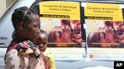 Une femme et son bébé passent devant les affiches de la campagne de vaccination contre le choléra dans un camp de déplacés à Beira, au Mozambique, le 3 avril 2019.