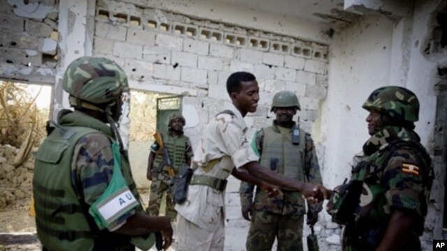 AMISOM commander, Major General Natham Mugisha (R) shakes hands with a commander from the Transitional Federal Government army a day after heavy fighting against the Al Shabaab insurgents in the Sigaale District of Mogadishu, 15 Dec 2010