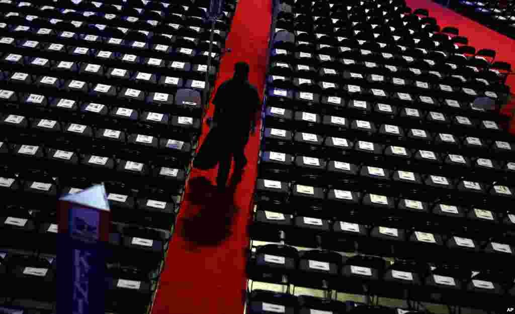 A worker walks down the aisle to collect trash on the floor at the convention.