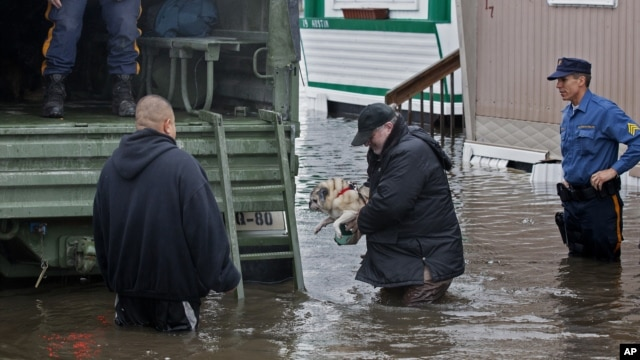 A man walks with his dog to a National Guard vehicle after leaving his flooded home in Moonachie, New Jersey, after Hurricane Sandy