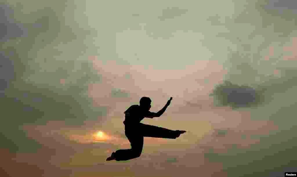 在斯里兰卡科伦坡,一名男孩在夕阳映照下在海滩练习空手道。